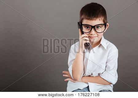 Serious little boy in glasses sitting and talking on mobile phone over grey background