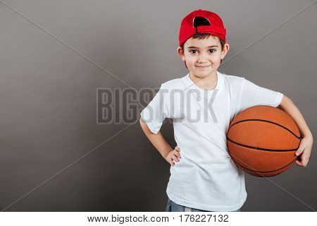 Portrait of smiling little boy in cap with orange basketball ball over grey background