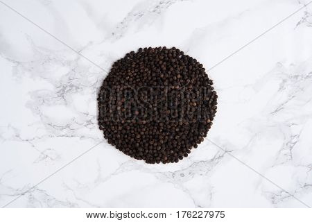 Top view of a black pepper heap on white marble table