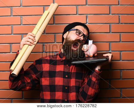 Bearded Caucasian Hipster Holding Laptop, Piggy Bank And Craft Paper
