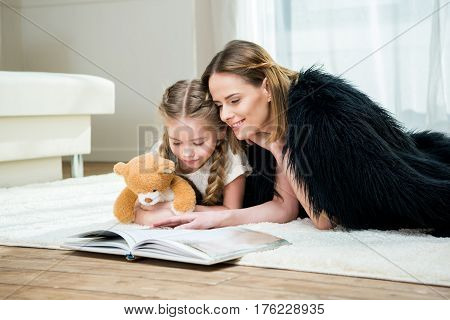 Smiling Mother And Daughter With Teddy Bear Reading Book On Carpet