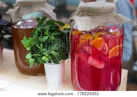 Closeup of lemonades with basil in glass jars at restaurant background. Refreshing drinks in craft containers on bar counter
