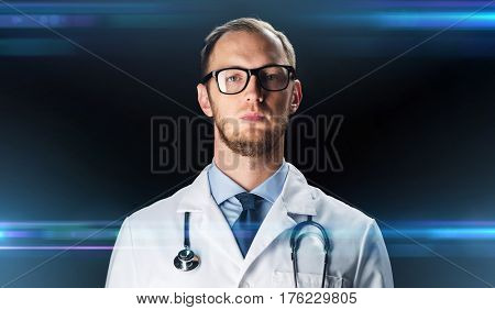 science, technology, people and medicine concept - close up of male doctor in white coat with stethoscope over dark background and laser light