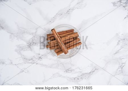 Top view of cinnamon sticks grouped in a bowl on white marble table