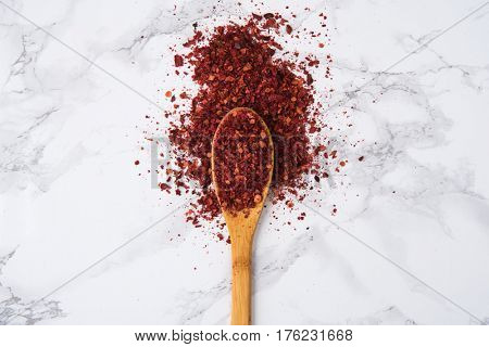 Red hot chilli pepper flakes in wooden spoon isolated on white marble background