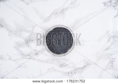 Top view of a blue poppy seeds in a bowl isolated on white marble table