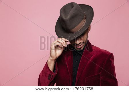 Close up portrait of a afro american man in hat posing isolated on the pink background
