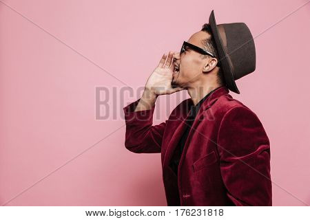 Side view portrait of a young african american man screaming out loud with hand at his mouth isolated on the pink background
