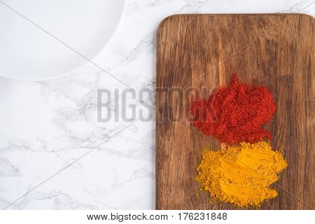 Top view of two turmeric and paprika heaps over wooden cutting board