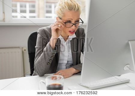 woman squeezing her eyes to see whats on computer