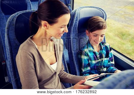 travel, tourism, family, technology and people concept - happy mother and son with tablet pc computer sitting in travel bus
