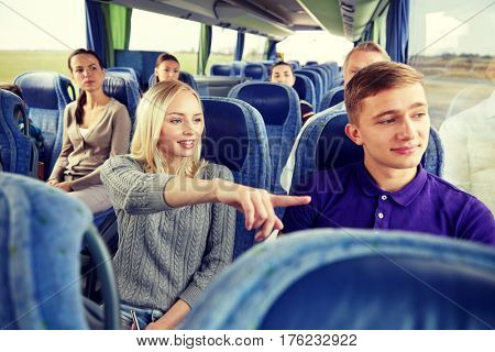 transport, tourism, road trip and people concept - young couple with group of tourists driving in travel bus and pointing finger to something outside