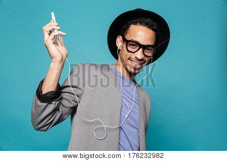 Portrait of a smiling african man having fun while listening to music with earphones over blue background