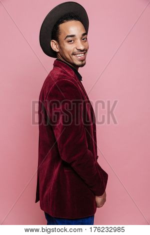 Stylish afro american man in hat and lacket looking at camera isolated on the pink background
