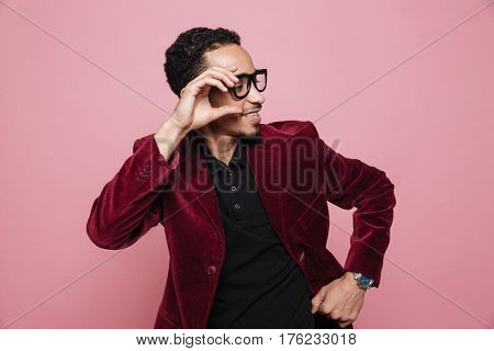 Portrait of a stylish handsome young afro american man in jacket posing and touching eyeglasses isolated on the pink background