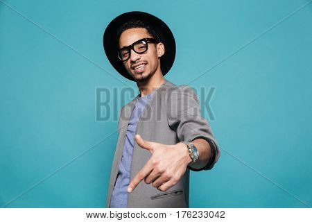 Portrait of a confident afro american man in eyeglasses and hat pointing finger at copyspace over blue background