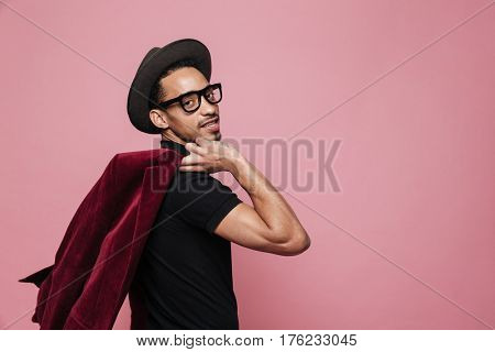 Portrait of a confident young afro american man in eyeglasses and hat holding jacket over his shoulder isolated on the pink background