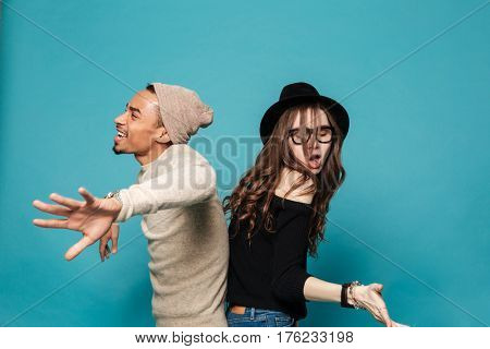 Happy young multiracial couple dancing isolated over blue background