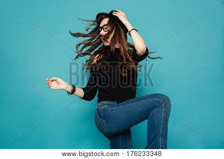 Portrait of a pretty modern young woman in black hat dancing and whirling over blue background