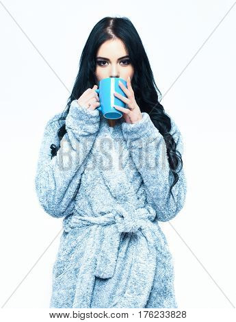 pretty serious cute sexy girl or beautiful woman with fashion makeup and curly long hair posing in blue velour bathrobe with cup isolated on white background