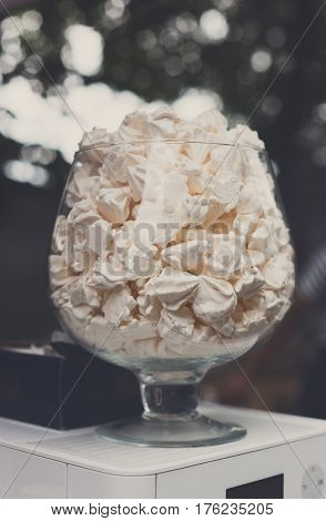 Desserts choice. Meringue cookies in glass jar on counter bar for sale. Traditional french sweets for sale, closeup, vertical image