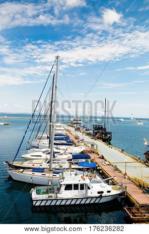 Sailing ships and yachts stand moored in marina port sunny day cloudy sky