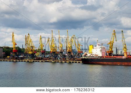 Industrial port with cranes. Port cargo cranes over the cloudy sky background