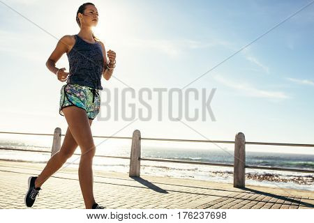 Female runner running along the road by the sea. Fitness woman jogging on the sea side promenade.