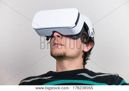 Portrait of man in virtual reality glasses. Male person wears VR headset
