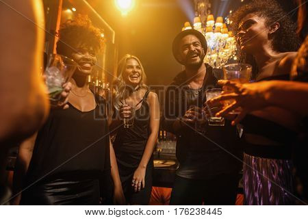 Group of young people having party at pub. Friends having cocktails in night club.