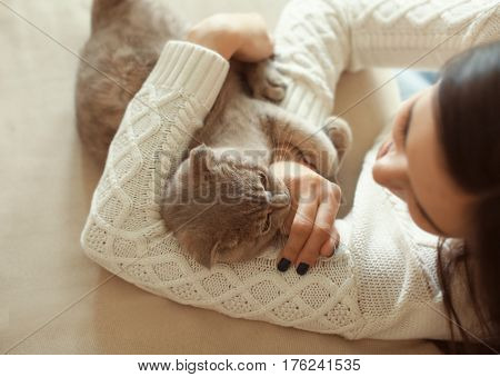 Young woman playing with cute cat at home