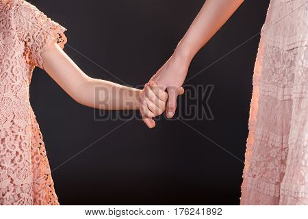 Close-up partial view of mother and daughter holding hands on black
