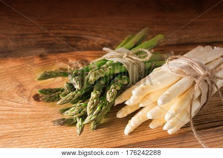 Bound green and white asparagus on rustic wood