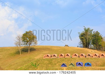 Dome tents on camping site on the mountain at Doi Samer Dao in Nan province Thailand evening sunlight