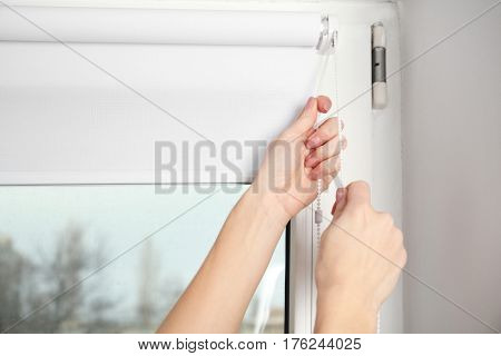 Woman hands installing window blinds, closeup