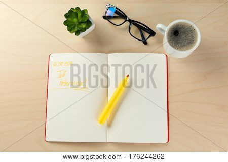 Job interview reminder in diary on wooden table