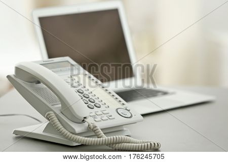 Telephone on table at workplace of technical support agent