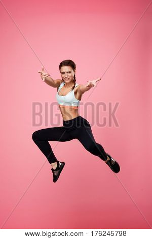 Funny girl in blue top and black pants juming like Spiderman, making faces looking straight