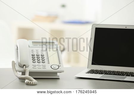 Telephone and laptop on table in office