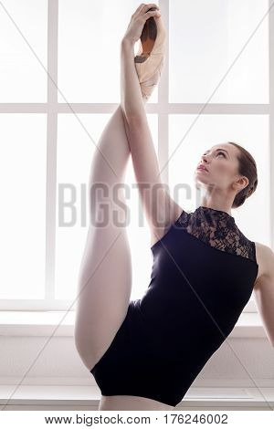 Classical Ballet dancer portrait. Beautiful graceful ballerine in black practice standing split stretching ballet position at window background. Ballet class training, high-key. Vertical image