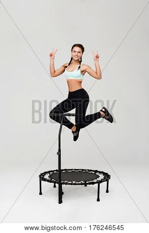 Young attractive athlete jumping on mini rebounder with handle smiling cheerfully isolated on grey background