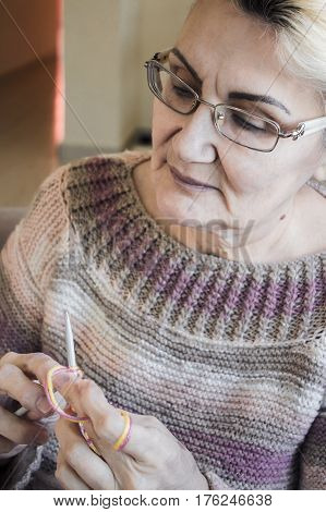 Old Women Looking At Her Hands Holding Knitting Needles And Colorful Thread In Her Hands To Tie A Sc