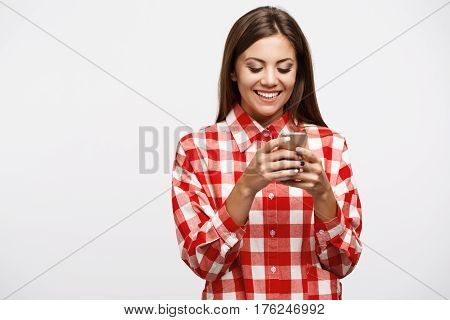 Girl in cool outfitl stuck on phone playing cool games having fun and texting friends