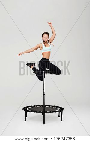Sporty girl jumping with hands up rebounder with handle looking straight isolated on grey background