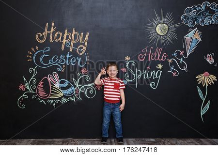 Smiling happy little boy standing and okay gesture over chalk board with colorful easter text background