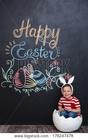 Happy little boy wearing rabbit ears and sitting inside big cracked eggshell over chalk board with easter doodles background