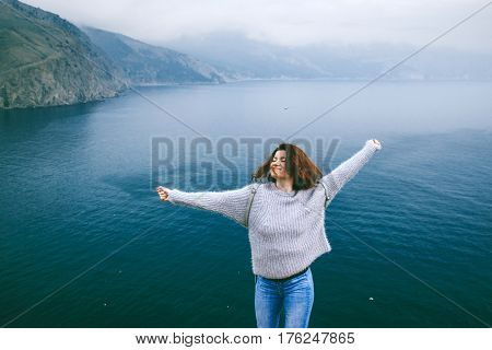 Girl wearing sweater travel by the sea alone. Cold weather, calm scene. Backpacker walking outdoors in spring, back view over landscape. Wanderlust photo series.