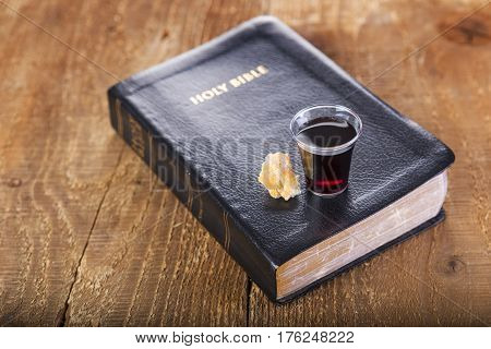 Taking Communion. Cup of glass with red wine bread and Holy Bible on wooden table close-up. Focus on glass.