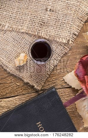 Taking Communion. Cup of glass with red wine bread and Holy Bible on wooden table close-up.