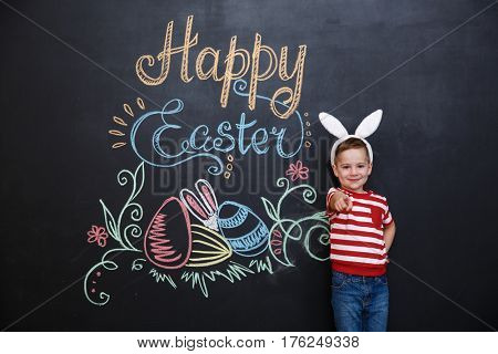 Little cute boy wearing bunny ears and pointing finger at camera over chalk board with easter doodles background